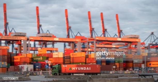 July 2020, Hamburg: Block storage facilities with gantry cranes are illuminated by the setting sun at Container Terminal Altenwerder in the Port of...