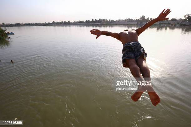 July 2020, Iraq, Baghdad: A man jumps into the Tigris River to cool off from the heatwave, at Baghdad's Al-Adhamiyah neighbourhood. Photo: Ameer Al...