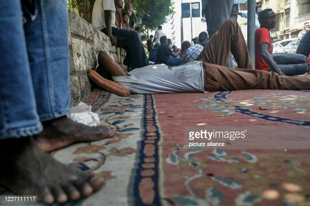 July 2020, Lebanon, Beirut: A Sudanese worker rests on the ground in front of his country's embassy after taking part in a protest at the Lebanese...