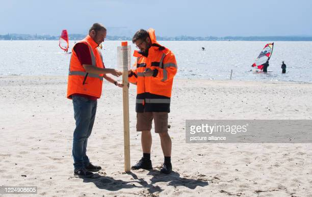 July 2020, Lower Saxony, Neustadt am Rübenberge: Employees of the City and Nature Park put up warning signs on the surfer beach near Mardorf am...