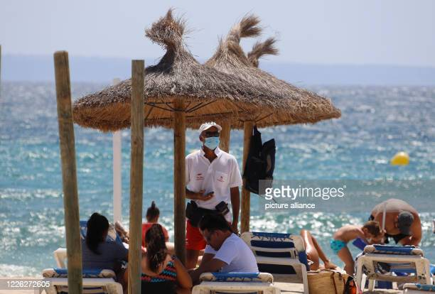 The employee of a beach chair rental company is standing under a parasol on Son Maties beach with a mouth and nose protection mask The regional...