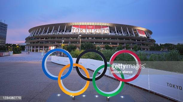 July 2021, Japan, Tokio: In the evening twilight Olympic rings stand in front of the Olympic Stadium. The Olympic Stadium is the sports venue of the...