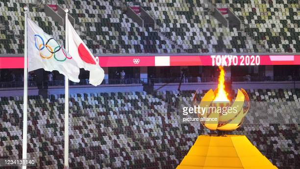 July 2021, Japan, Tokio: Olympia: Opening ceremony in the Olympic Stadium. The Olympic fire burns next to it the Olympic and Japanese flag. Photo:...