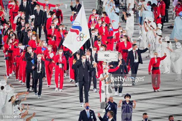 July 2021, Japan, Tokio: Olympics: Opening Ceremony at the Olympic Stadium. The Russian Olympic Committee team with flag bearers fencer Sofya...