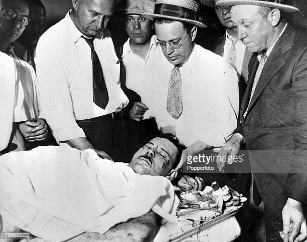 """The body of John Dillinger, America's """"Public Enemy No. 1,"""" lies on a slab in a morgue room, surrounded by policemen, after he was shot dead by..."""