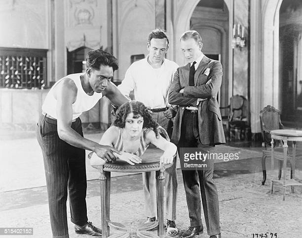 July 24, 1922. Learning to Swim on a Table. The world's champion speed swimmer, Duke Kahanamoku teaching Miss Lura Anson to swim, while director Sam...