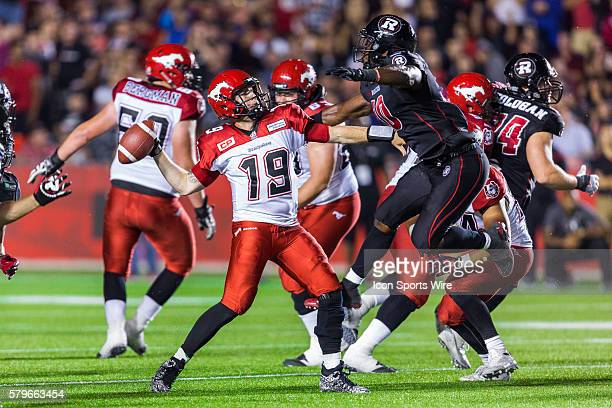 Calgary Stampeders Bo Levi Mitchell with Ottawa RedBlacks Malik Jackson during Canadian Football League action between the Calgary Stampeders and...