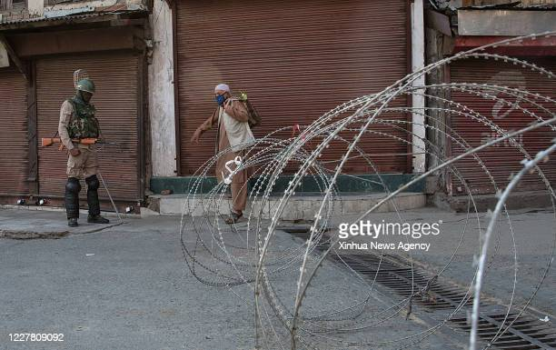 July 24, 2020 -- A man wearing a face mask crosses a barricade as an Indian paramilitary trooper stands guard in Srinagar city, the summer capital of...