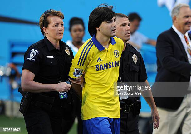 A Chelsea fan gets taken off the field in handcuffs after jumping onto the field from the stands at the end of the International Championships Cup...