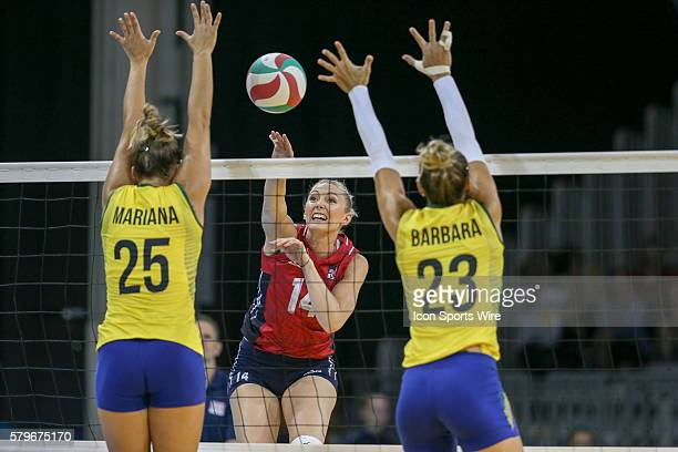 Nicole Fawcett 14 of the United States hits against Mariana Costa and Barbara Bruch of Brazil during the Women's Volleyball Gold Medal match at the...