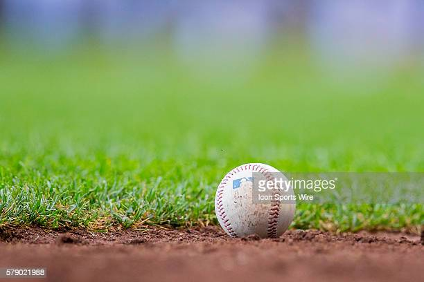 A MLB baseball sits on the dirt during a game between the Cincinnati Reds and the New York Mets at Miller Park in Milwaukee WI