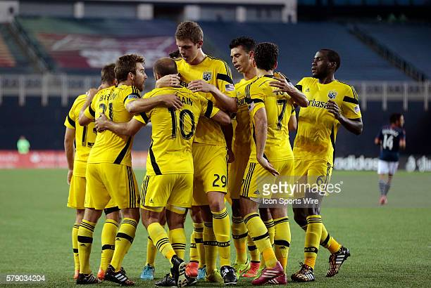 Teammates mob Columbus Crew's Federico Higuain after his opening goal The Columbus Crew defeated the New England Revolution 21 in a regular season...