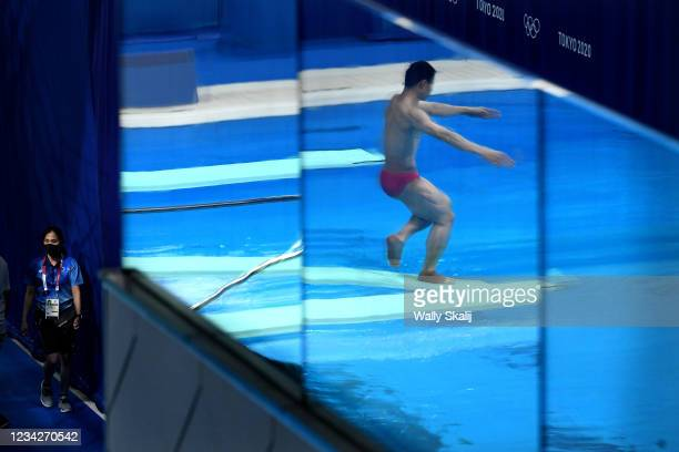 July 26, 2021: A diver practices before the mens synchronized 3m springboard final as a volunteer looks on in the 2020 Tokyo Olympics.