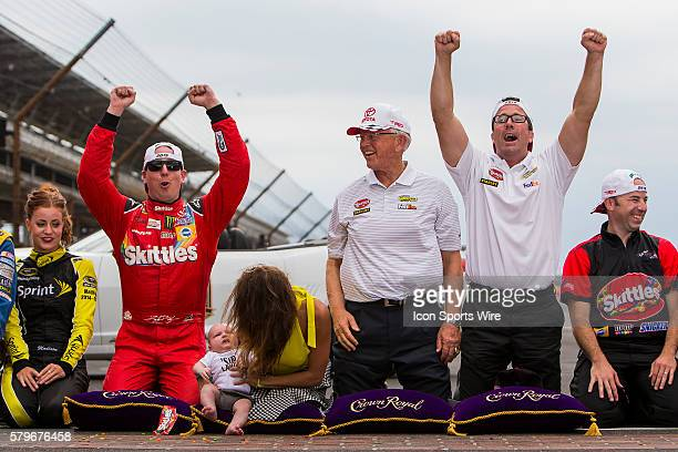 Kyle Busch driver of the Skittles Toyota celebrates after kissing the bricks with his wife Samantha Busch son Brexton Busch Team Owners Joe and JD...
