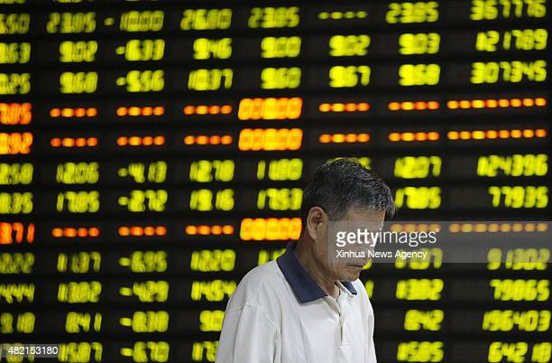 July 27, 2015-- A man pays attention to stock market quotation at a business lobby of a security company in Huaibei, east China's Anhui Province,...