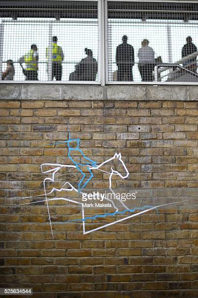 July 30, 2012 - London, England, United Kingdom - With the Olympic logo for equestrian painting to the wall below, passengers await the DLR n the...