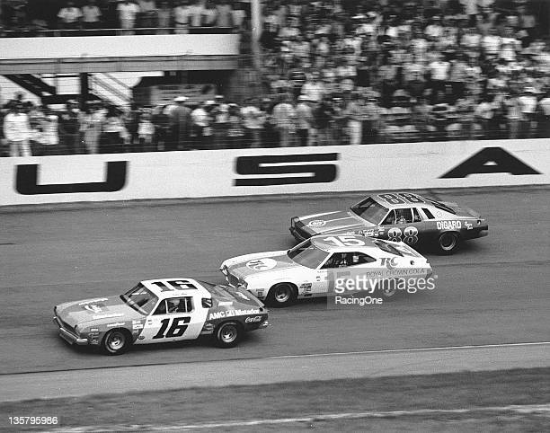 Bobby Allison driving Roger Penske's AMC Matador leads Buddy Baker and brother Donnie Allison through the trioval of Daytona International Speedway...