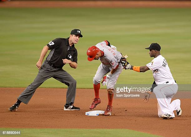 Cincinnati Reds center fielder Billy Hamilton is safe in second base as Miami Marlins shortstop Adeiny Hechavarria is trying to tag him during a game...