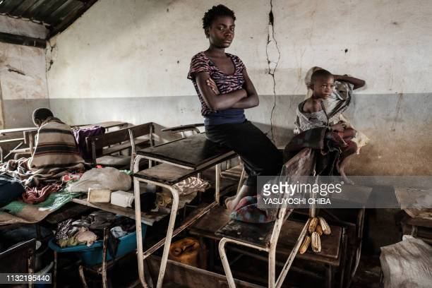 Juma Luis Elia sits on a school desk where she sleeps at a local school where she took shelter in Buzi Mozambique on March 23 after the area was hit...
