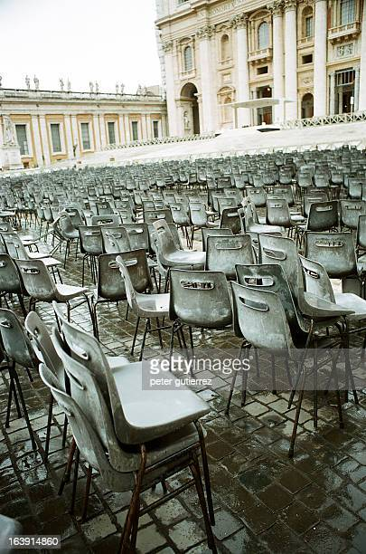 Jumble of wet plastic chairs on wet cobblestones, St. Peter's Square, Vatican City, Rome, Italy.