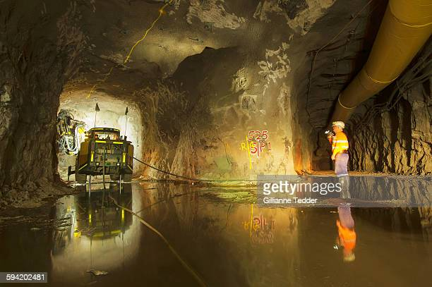 jumbo drill rig and reflection with miner - underground mining stock photos and pictures