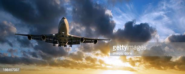 XXL jumbo jet airplane landing at sunset