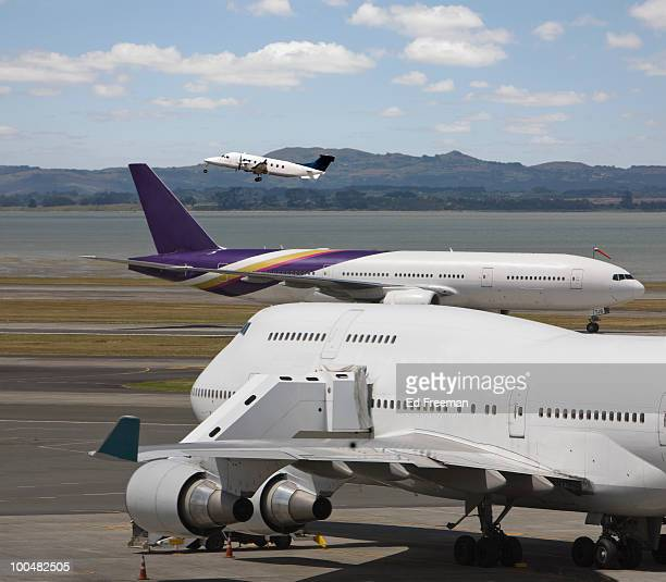 jumbo jets on ground and private jet taking off - auckland stock pictures, royalty-free photos & images