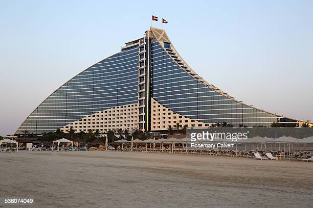Jumeirah Beach Hotel shaped like a wave with sandy beach in foreground Dubai United Arab Emirates