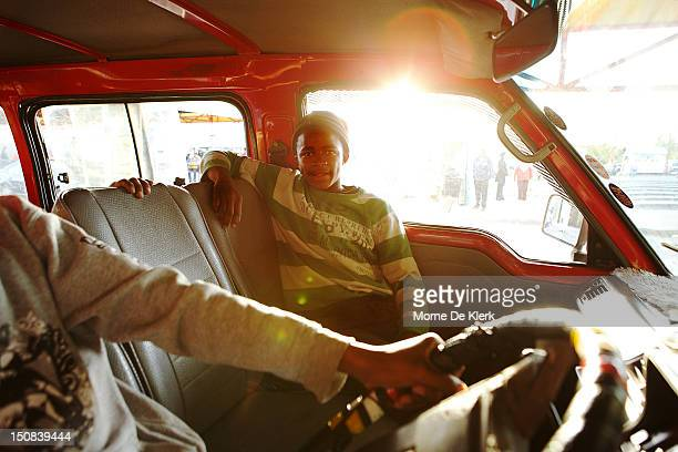 Jump Boy sits in the passenger seat of a taxi on July 05 2012 in Upington South Africa Jump boys are assistants to taxi drivers and help commuters on...