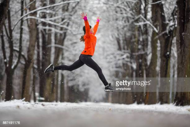 jump! - side view woman jumping for joy in winter - jumping stock pictures, royalty-free photos & images