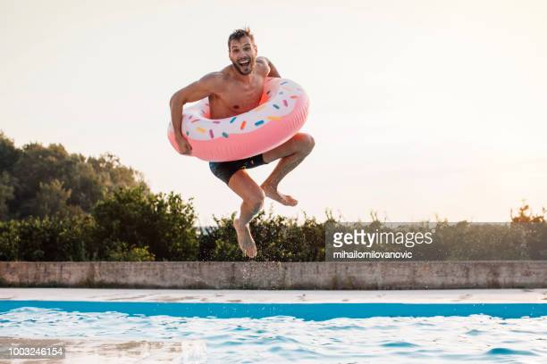a jump with inflatable ring - pool stock pictures, royalty-free photos & images