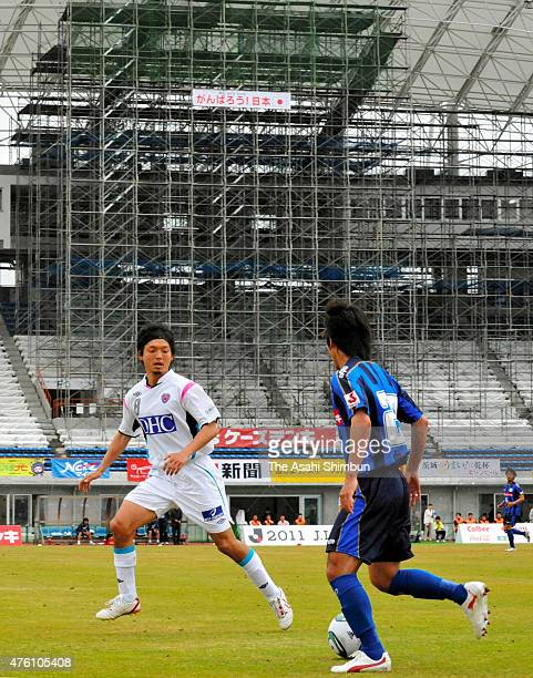 Jumpei Obata of Mito Hollyhock and Ryota Nagata of Sagan Tosu compete for the ball while the restoration work of the stadium continues during the...