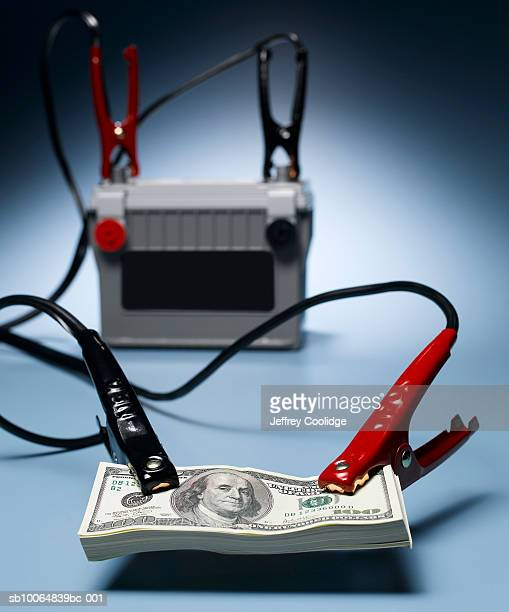 Jumper cables connected to car battery and stack of US one hundred dollar bills