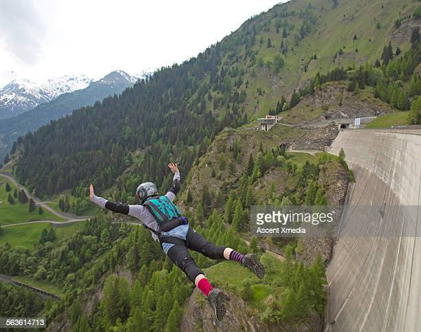 BASE jumper in free fall down face of concrete dam