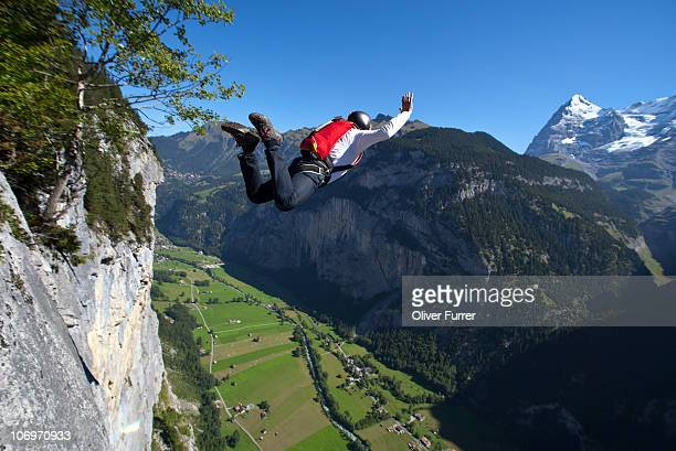 BASE jumper is diving into the valley from a cliff