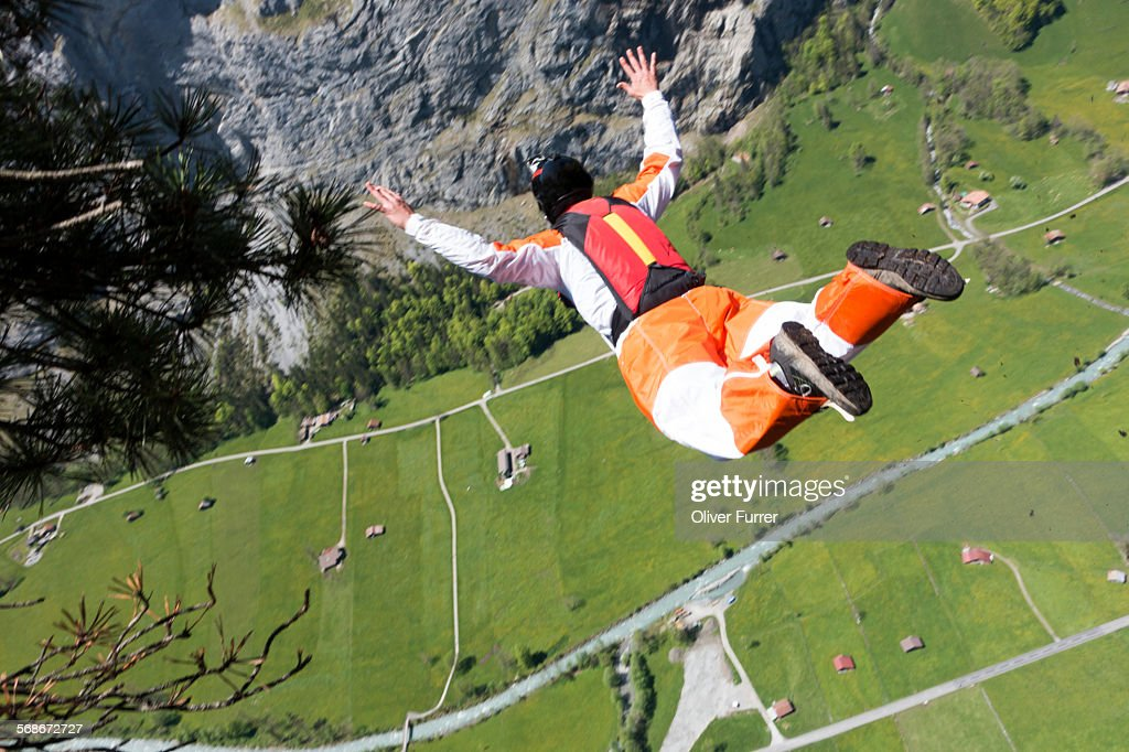 BASE jumper kicks off a cliff down into the valley : Stock Photo