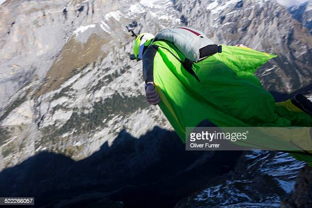 BASE jumper with a wingsuit is diving of a cliff.