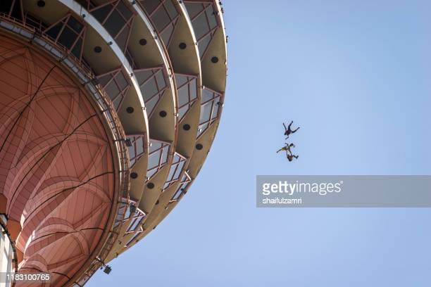 a base jumpers in jumps off from kl tower at kuala lumpur, malaysia. - shaifulzamri stock pictures, royalty-free photos & images