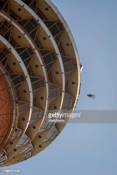 a base jumpers in jumps off from kl tower at kuala lumpur, malaysia - shaifulzamri stockfoto's en -beelden