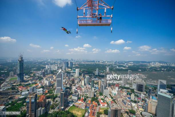 a base jumpers in jumps off from kl tower at kuala lumpur, malaysia - shaifulzamri stock pictures, royalty-free photos & images