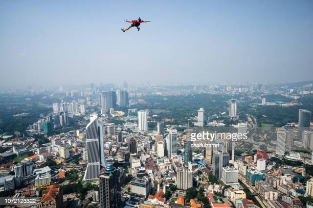 a base jumpers in jumps off from kl tower. kl tower base jump is an annually event and participants from experienced base jumpers from all around the world. - shaifulzamri stock pictures, royalty-free photos & images