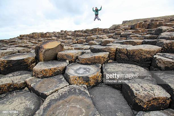 jumping at the famous basalt columns of giant's causeway, northern ireland, uk - giant's causeway stock pictures, royalty-free photos & images