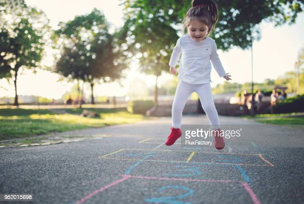 jumping child playing hopscotch - hopscotch stock pictures, royalty-free photos & images