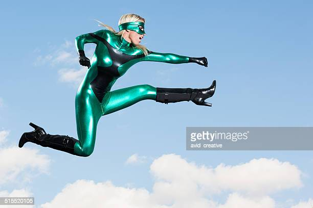 jumping: female super hero flying punch kick - superhero stock pictures, royalty-free photos & images