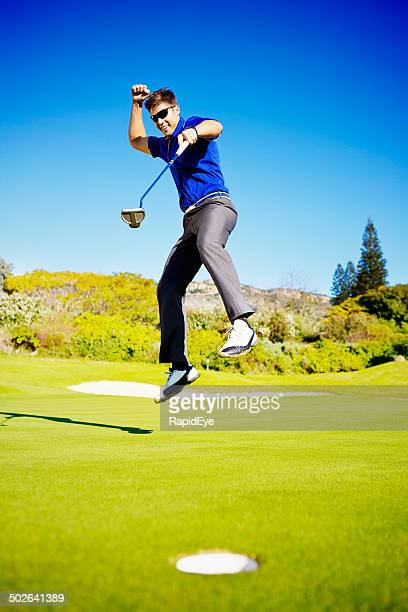 Jumping for joy, young golfer celebrates gets the ball in!