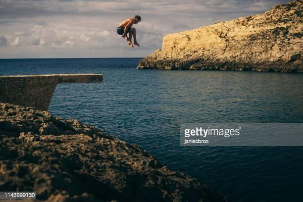 pulando de uma costa alta. divertimento do verão - no alto - fotografias e filmes do acervo