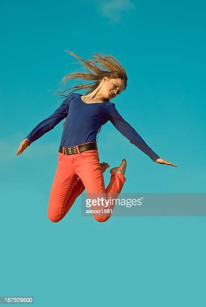 La fille de saut sur un ciel bleu en arrière-plan
