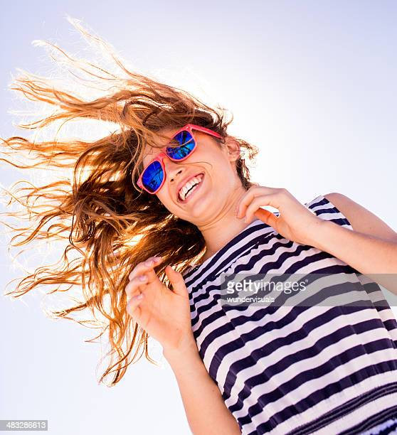 Jumping girl with blue sky and sunflare