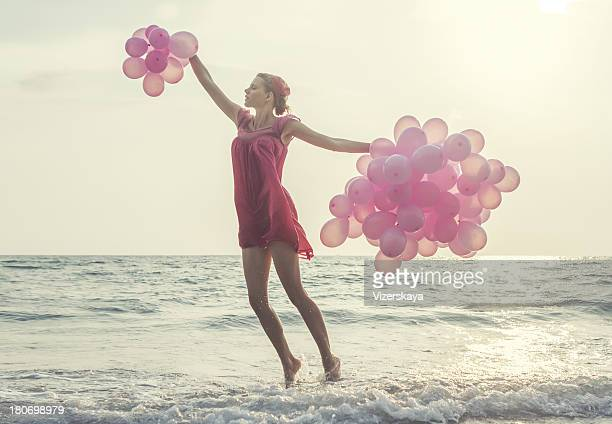jumping girl with pink balloons