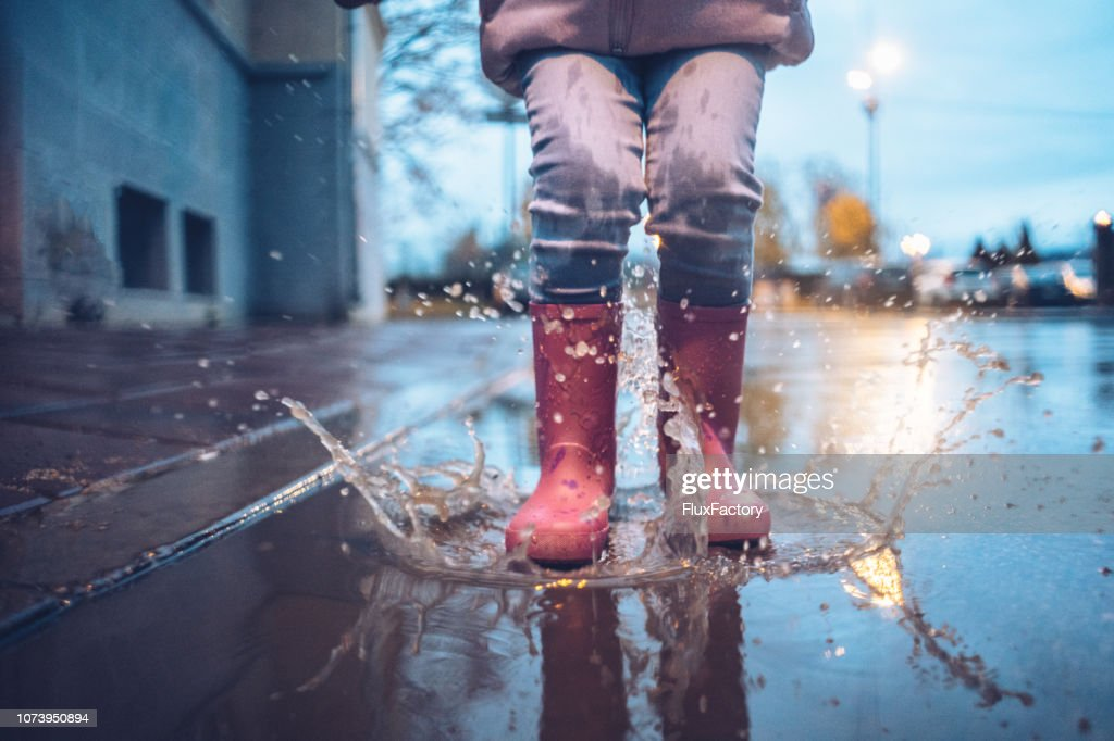 Jumping in puddle and having fun : Stock Photo